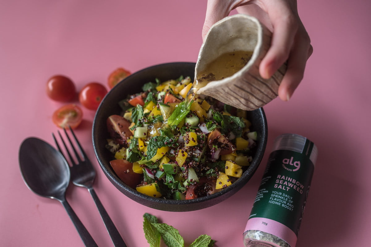 Quinoa Salad with Seaweed Dressing Pouring Into the Bowl